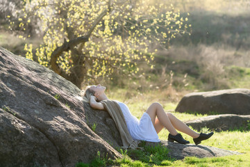 hipster teen sits on the grass outdoor near large stone. Magic landscape