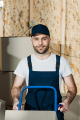 Smiling delivery man holding hand truck