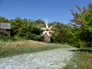 Ukraine, Pyrohiv (Kiev) - September 17, 2017: A wooden antique windmill stands near a forest and a paved road in the Museum of Folk Architecture and Life