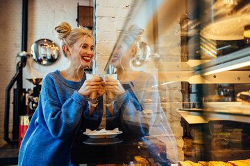 Friendly european blond woman with two bunch hairstyle taking coffee latte from the showcase at cozy bakery coffee shop. Morning service client customer consumer consumerism buying concept.