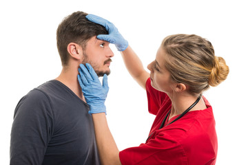 Female doctor checking male patient eye.