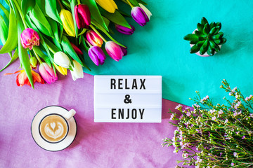 Relax & Enjoy written in lightbox with spring flowers from above