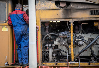 workers repair diesel locomotive engine