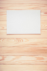 Retro old textured paper blank hanging on wooden wall background. Vintage style filtered photo