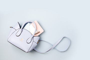 Wall Mural - Cute blue handbag with , notebook and feminine accessories . Flat lay, top view. Spring fashion concept in pastel colored
