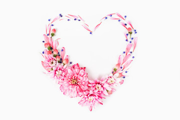 Beautiful floral arrangements. Pink chrysanthemums in the shape of heart frame on white background. Flat lay, top view.