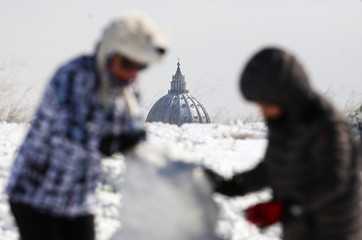 People play with the snow as Saint Peter's Basilica dome is seen in the background after a heavy snowfall in Rome