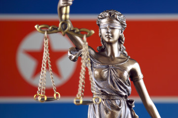 Symbol of law and justice with North Korea Flag. Close up.
