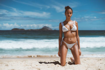 Hottie young serious African American female is standing on knees on sand of a beach with ocean, horizon, and islands in defocused background; copy space place for logo, text message or advertising