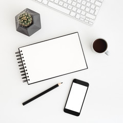 White desk, table with spiral notebook, coffee, cactus and smartphone screen for mock up or product monage. Flat lay.