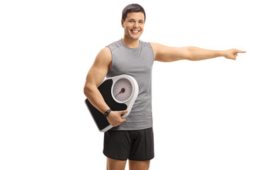 Young man in sportswear holding a weight scale and pointing