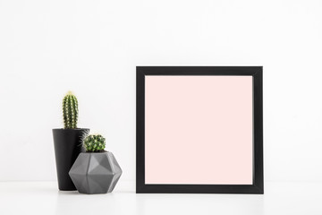Photo frame mock up and a cactus on a white table.