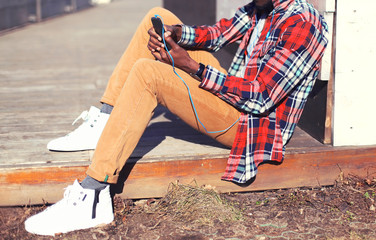 Fashion man listens to music using the smartphone sitting in the city close-up