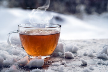 steaming hot tea in a glass cup is standing outside on a cold winter day with snow, copy space