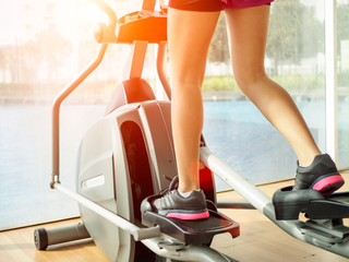 Close up woman legs working out on the exercise bike in fitness gym. exercise concept.