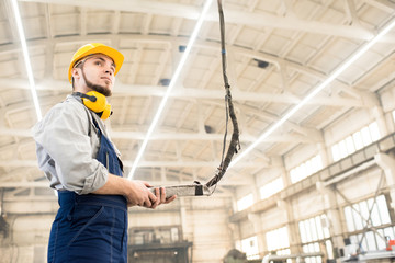 Low angle view of bearded machine operator wearing overall and protective helmet wrapped up in work while standing at spacious production department of modern plant