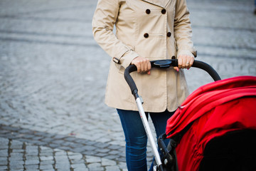 Young mother walking with baby carriage at the street