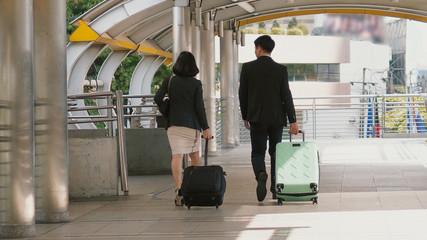 Back of business people drag baggage and walking on bridge