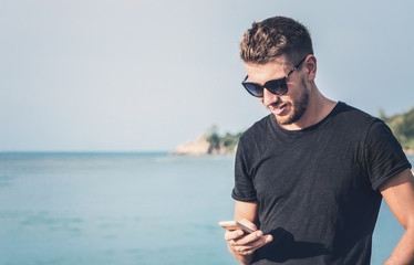 Handsome man in sunglasses holding mobile phone in his hand and texting message, on tropical background.