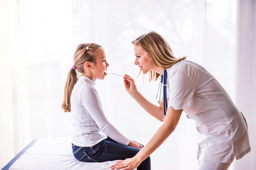Young female doctor examining a small girl in her office.