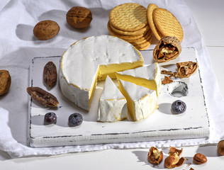 round Camembert cheese on a white wooden board, next to sausage