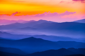 quiet mountain valley in a blue mist at the sunset