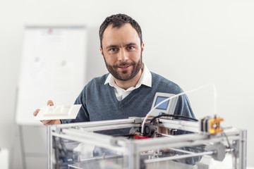 Great result. Handsome bearded young man holding a 3D model and posing with it for the camera while standing near the 3D printer and smiling pleasantly