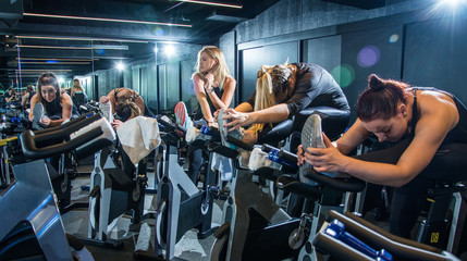 Group of young women in sportswear stretching their legs on exercise bikes before cycling class in health club.
