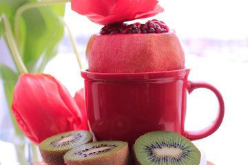 Healthy lifestyle. Diet. Juicy red fresh pomegranate and kiwi. Nature concept. Red tulips on background. Copy space