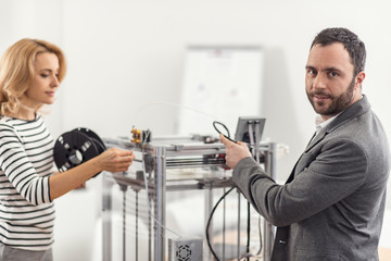 Thorough preparation. Handsome bristled young engineer posing for the camera while preparing 3D printer for work together with his female colleague