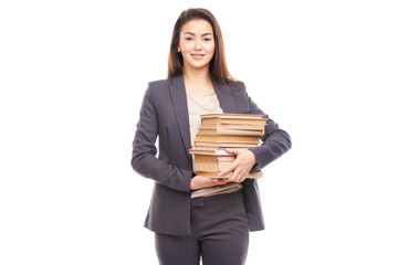 Portrait of young businesswoman holding stack of books