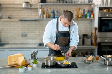 chef in apron stirring ravioli pasta in frying pan on burner in restaurant kitchen