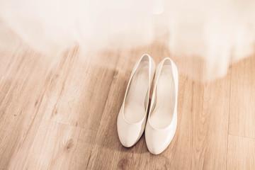 White wedding bridal shoes under the dress