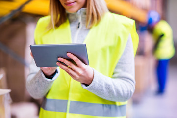 Unrecognizable woman warehouse worker with tablet.