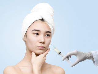 Studio portrait of young attractive asian woman after spa with syringe doing skincare procedures. Beauty, healthcare, skincare concept