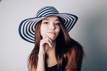 Sexy woman in striped hat on white background looking at the camera.