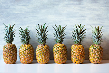 Ripe pineapples on white wooden background