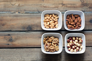 Four kinds of nuts in white bowls.