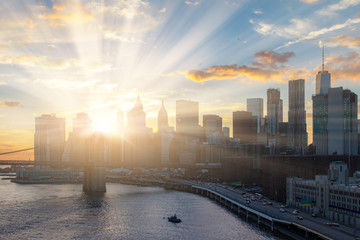 Sunlight shines behind New York City skyline