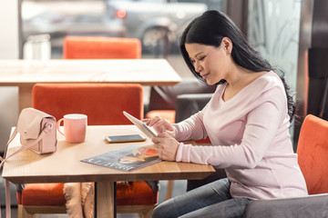 Pleasant entertainment. Delighted nice pleasant woman holding a tablet and looking at its screen while enjoying her time