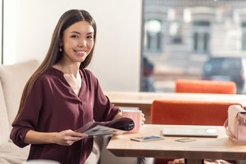 Confident businesswoman. Joyful nice confident woman holding a magazine and looking at you while having coffee