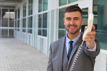 Businessman handing you a corded telephone