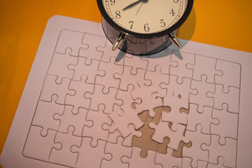 business background white jigsaw placed on orange table with clock and copy space. image for texture, problem, thinking, idea, toy, time, success, game concept
