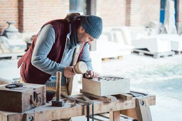 Steinmetz bearbeitet Sandstein in seiner Werkstatt
