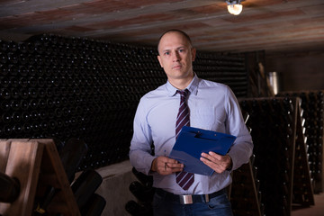 Winemaker with clipboard in winery vault