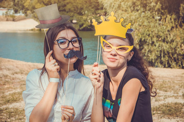 Two young women posing using photo booth props