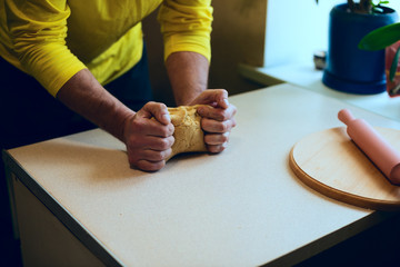 Strong male hands knead the dough on the white table