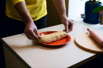 Men's hands put a piece of dough on a red plate