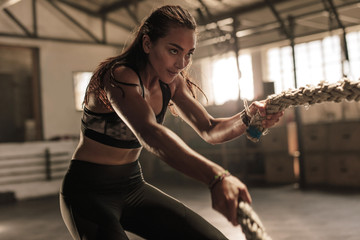 Fitness woman using battle ropes for exercising Wall mural