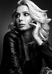 Black and white sensual portrait of a beautiful young woman. Blonde in a leather jacket on a dark background